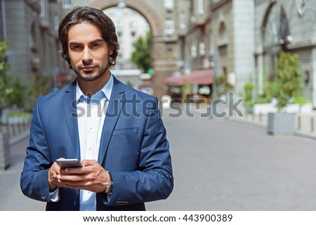 Handsome man using telephone outdoors