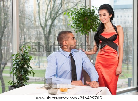 Handsome man waiting woman and looking back. woman standing behind late to date - stock photo