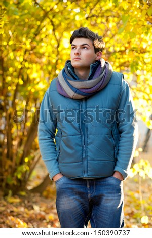 Handsome man walking in autumn park.