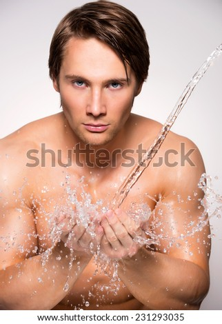 Handsome man washing his face with clean water on gray background. - stock photo