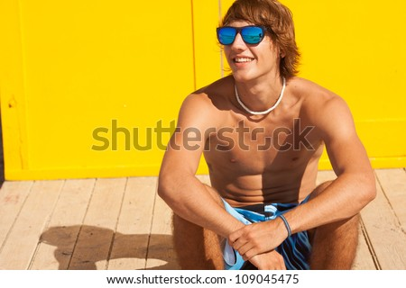 handsome man watching the sea on a lifeguard house - stock photo