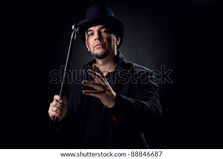 Handsome man wearing black hat and jacket holding stick over black background - stock photo