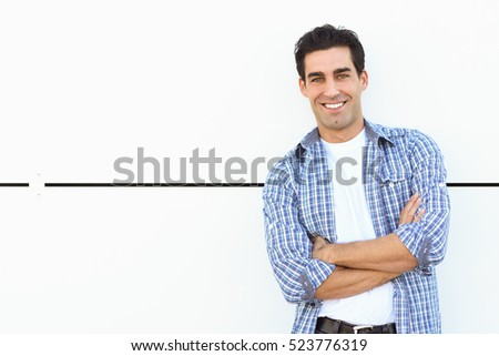 Handsome man wearing blue plaid shirt with arms crossed on white urban background.