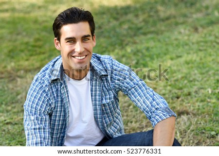Handsome man wearing casual clothes sitting on grass of an urban park.
