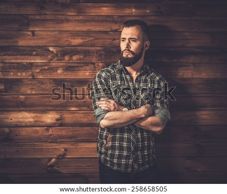 Handsome man wearing checkered  shirt in wooden rural house interior  - stock photo