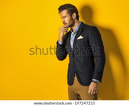 handsome man wearing jacket on yellow background - stock photo