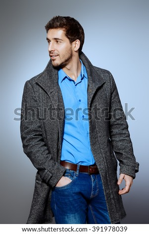 Handsome man wearing jeans clothes and a coat posing at studio. Men's beauty, seasonal fashion. Studio shot. - stock photo