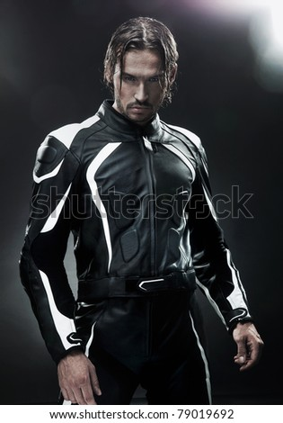 Handsome man wearing motorbike uniform - stock photo