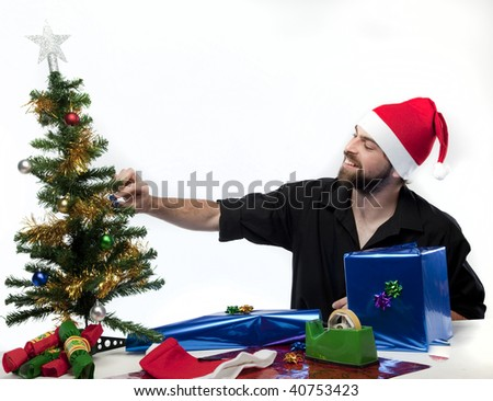 Handsome man wearing Santa Claus hat preparing gifts.