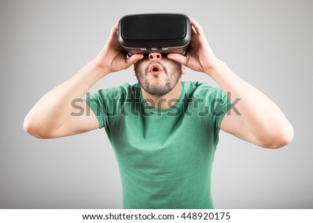 Handsome man wearing virtual reality glasses  isolated on a gray background - stock photo