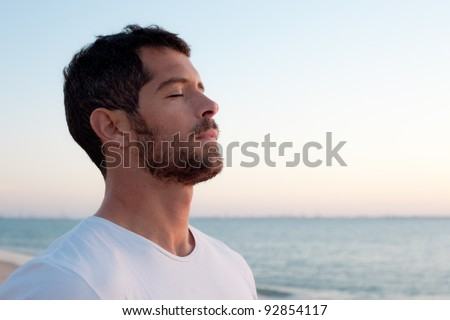 Handsome man wearing white deep breathing in front of the ocean. - stock photo