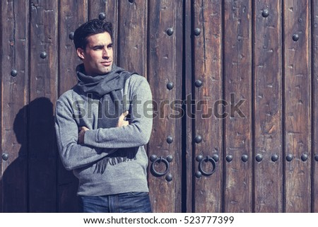 Handsome man wearing winter clothes in wooden background. Young male with sweater and scarf.