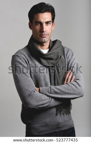 Handsome man wearing winter clothes smiling on white background. Young male with sweater and scarf looking at camera. Studio shot