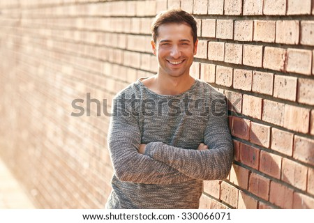 Handsome man with a friendly smile leaning casually against a brick wall with a rough texture outdoors - stock photo