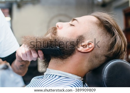 Handsome man with a long beard in barbershop