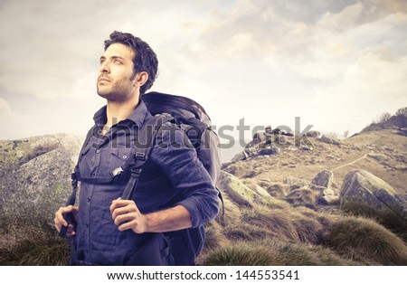 handsome man with a sack on his back walking in the mountains - stock photo
