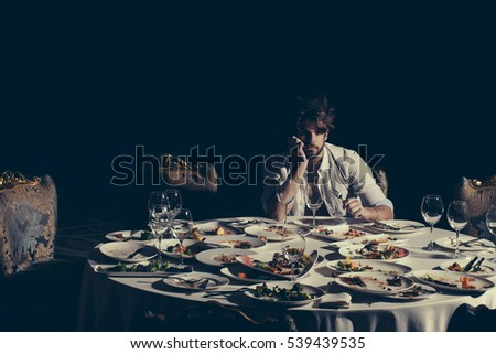 Handsome man with beard and blond messy hair bored or tired at table with leftovers or residues food on dirty plates after banquet dinner in restaurant on dark background