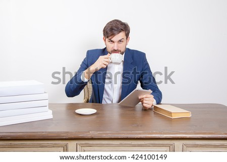 Handsome man with beard and brown hair and blue suit and tablet pc computer and some books and cup drinking coffee or tea sitting in the office and looking at camera.  Isolated on white background.   - stock photo