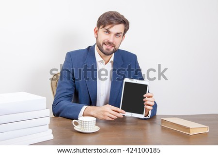Handsome man with beard and brown hair and blue suit and tablet pc computer and some books in the office holding tablet and showing display screen.  Isolated on white background.   - stock photo