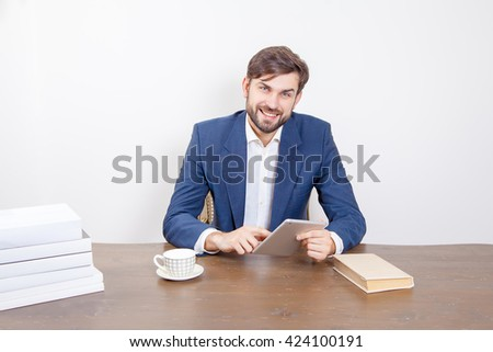 Handsome man with beard and brown hair and blue suit and tablet pc computer and some books looking at camera with smile and holding tablet in the office.  Isolated on white background.   - stock photo