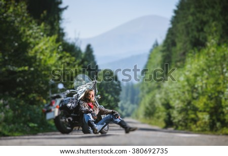 Handsome man with beard and long hair sitting next to a traveler motorcycle on an open road. Guy is wearing leather jacket and blue jeans. Sunny summer day in the mountains. Tilt shift soft effect - stock photo