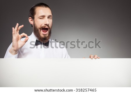 Handsome man with beard is advertising empty white billboard. He is standing and showing okay sign. He is winking and opening his mouth with joy. Isolated and copy space in right side - stock photo