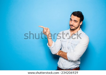 handsome man with beard pointing in one direction on a blue background - stock photo