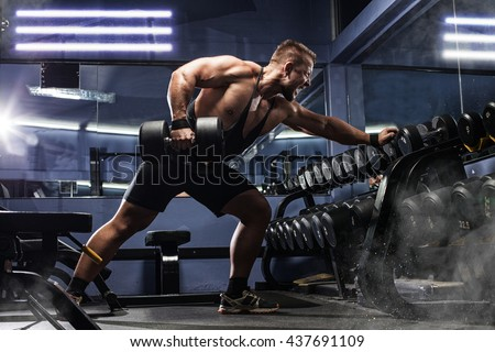 Handsome man with big muscles, posing at the camera in the gym - stock photo