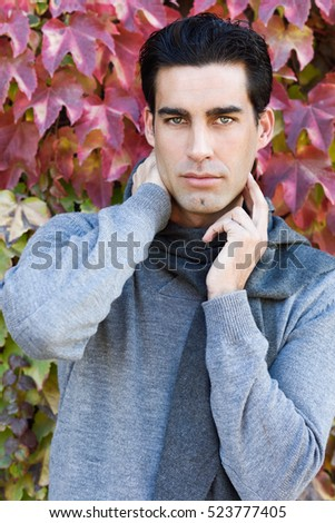 Handsome man with blue eyes wearing winter clothes in autumn leaves background. Young male with sweater and scarf.