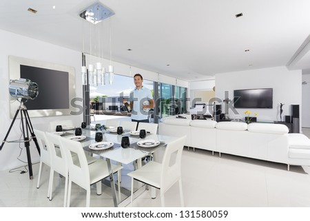 Handsome man with champagne bottle in luxury apartment - stock photo