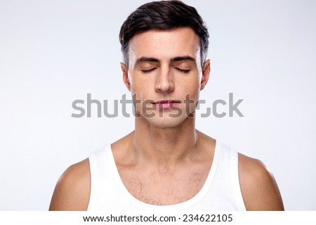Handsome man with closed eyes over gray background - stock photo