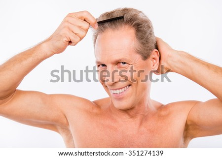 Handsome man with comb making his hairdress