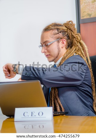Handsome man with dreads and business suit sitting by desk looking at wrist watch, young manager concept