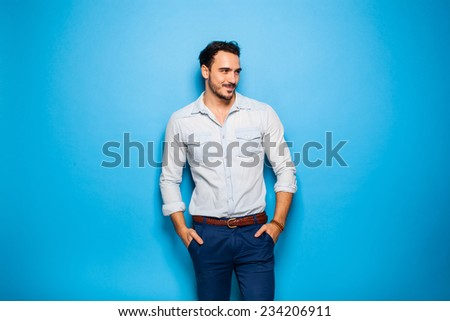 handsome man with hands in pockets looking relax in one direction - stock photo