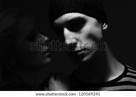 handsome man with hat whispers to him a young woman - stock photo