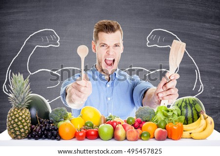 Handsome man with kitchenware vegetables and drawn muscles
