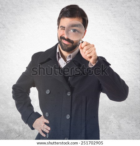 Handsome man with magnifying glass - stock photo