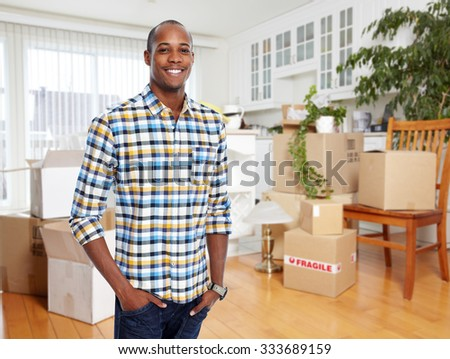 Handsome Man with moving boxes in new modern apartment. - stock photo