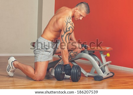 Handsome man with muscles lift a dumbbell on a seat trainer