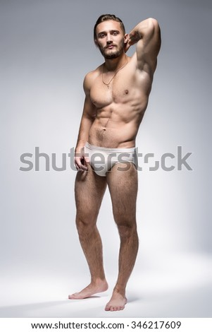 Handsome Man With Muscular Body Posing On Gray Background