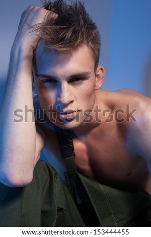 Handsome man with muscular torso, attractive face and fashionable hairstyle, dressed in dark green coveralls, with hand in his hair looking at camera - stock photo