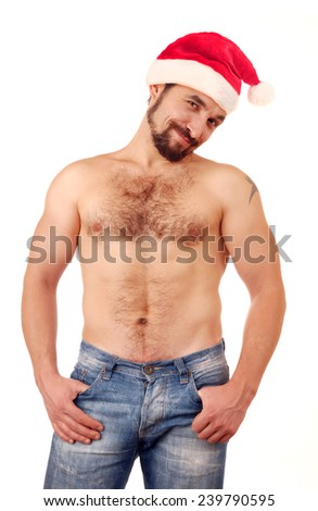 Handsome man with naked torso in Santa hat.