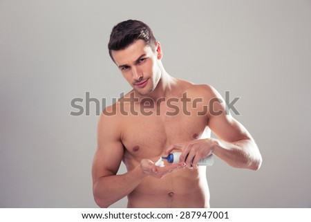 Handsome man with perfect skin using cream over gray background. Looking at camera