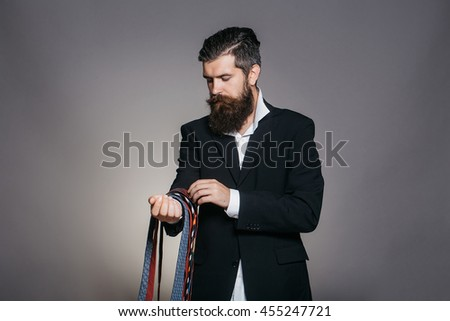 Handsome man with serious face and splendid beard in elegant jacket hanging many colorful ties on his hand posing on gray background studio