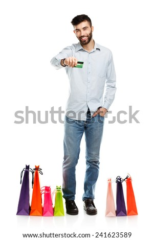 Handsome man with shopping bags and holding credit card. Christmas and holidays concept - stock photo