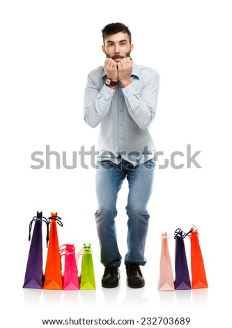 Handsome man with shopping bags is shocked. Christmas and holidays concept - stock photo
