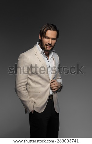handsome man with sly smile smoking cigar - stock photo