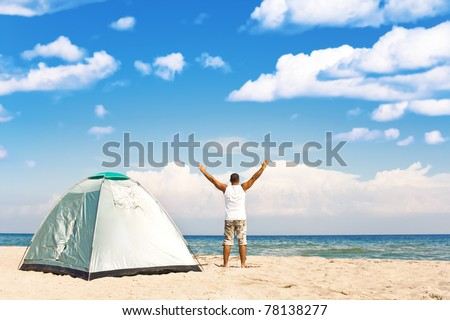 handsome man with tent enjoying camping recreation at a wonderful tranquil beach - stock photo
