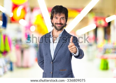 Handsome man with thumb up on unfocused background - stock photo
