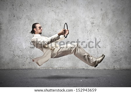 handsome man with white dress driving an imaginary car - stock photo